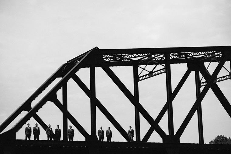 groomsmen standing on a bridge
