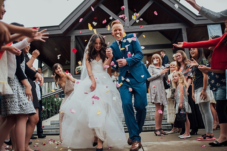 guest throwing flower petals at bride and groom