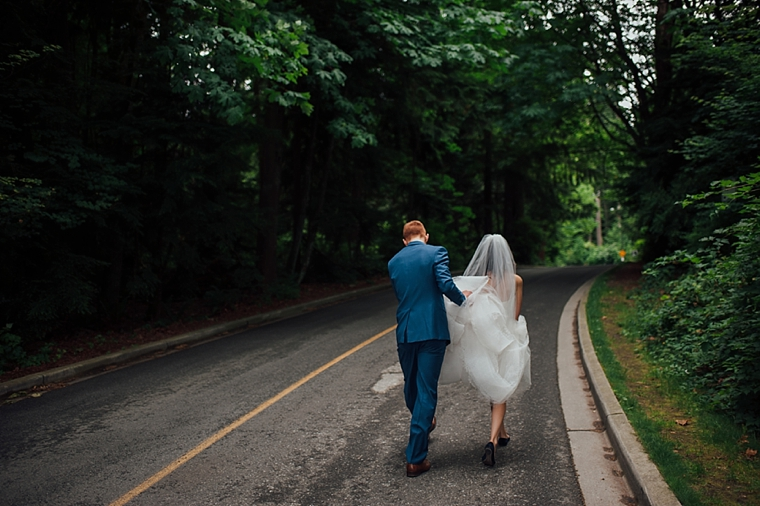 bride and groom walking down a forest road