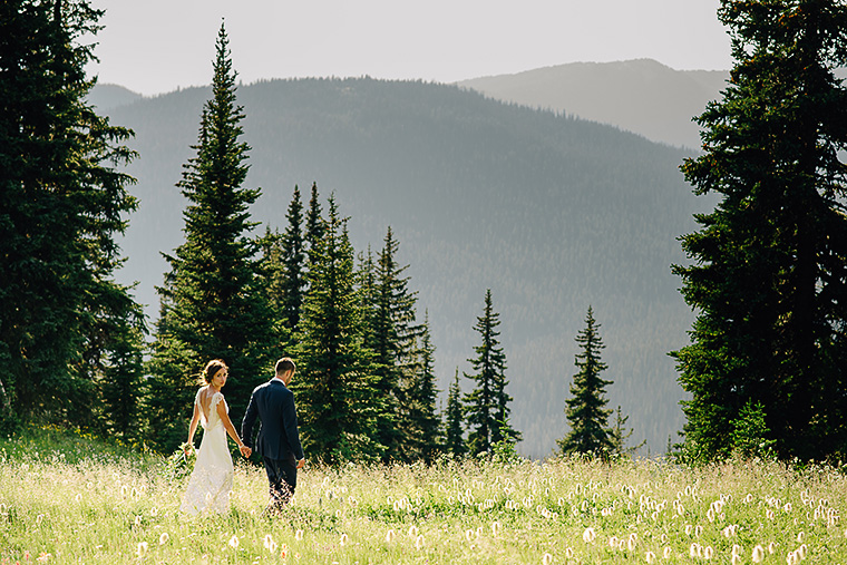 bride and groom walking through field in the forest
