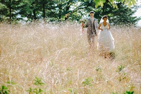 bride and groom walking through grass field