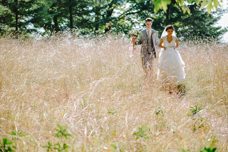 bride and groom walking through grass field
