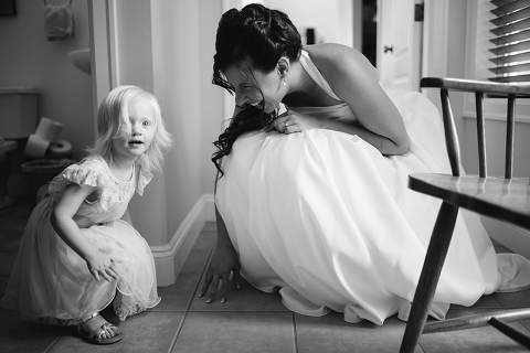 candid wedding moment with flowergirl