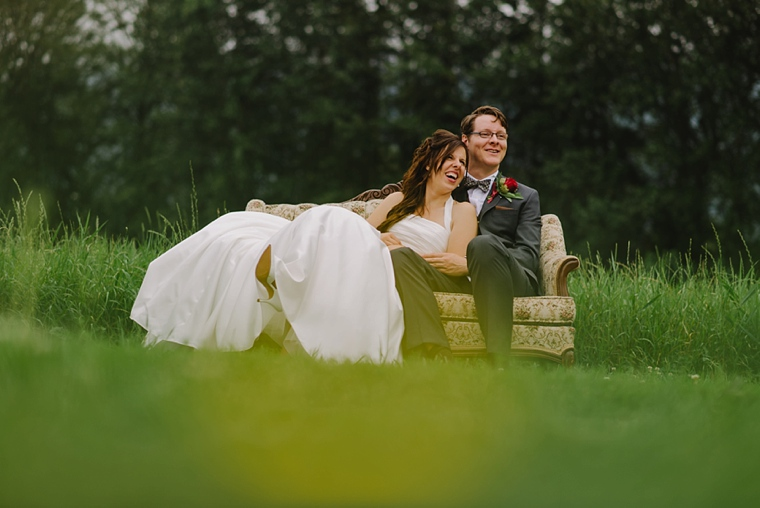 bride and groom sitting on a sofa in a field