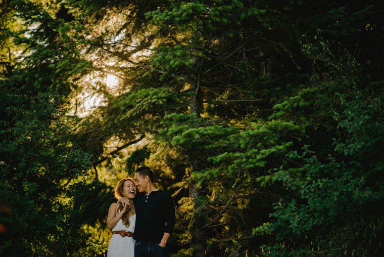 couple laughing walking through forest