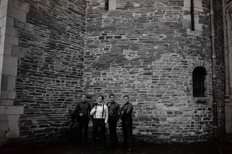 groomsmen portrait in front of european castle
