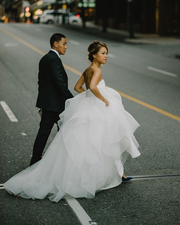 bride and groom crossing the street in vancouver