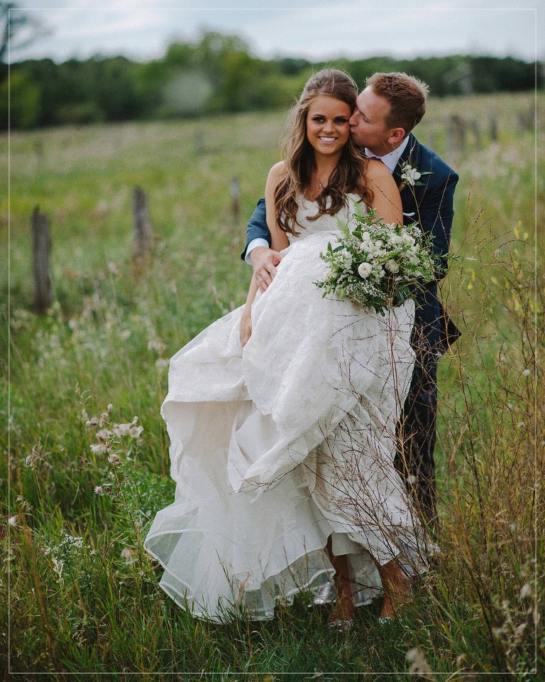 groom kissing bride in a winnipeg field on their wedding day
