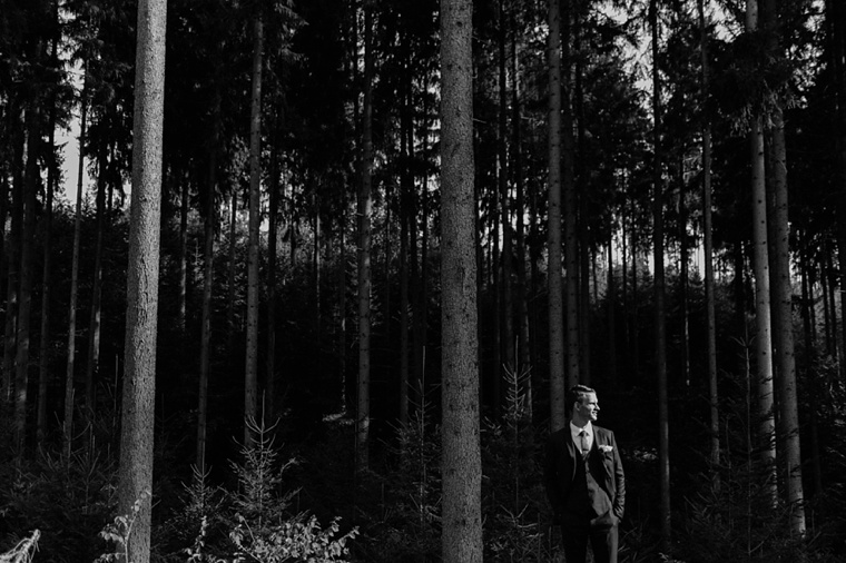 groom standing in the forest