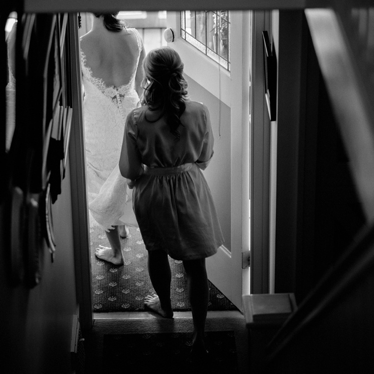 Black and white photo of bride walking out the door