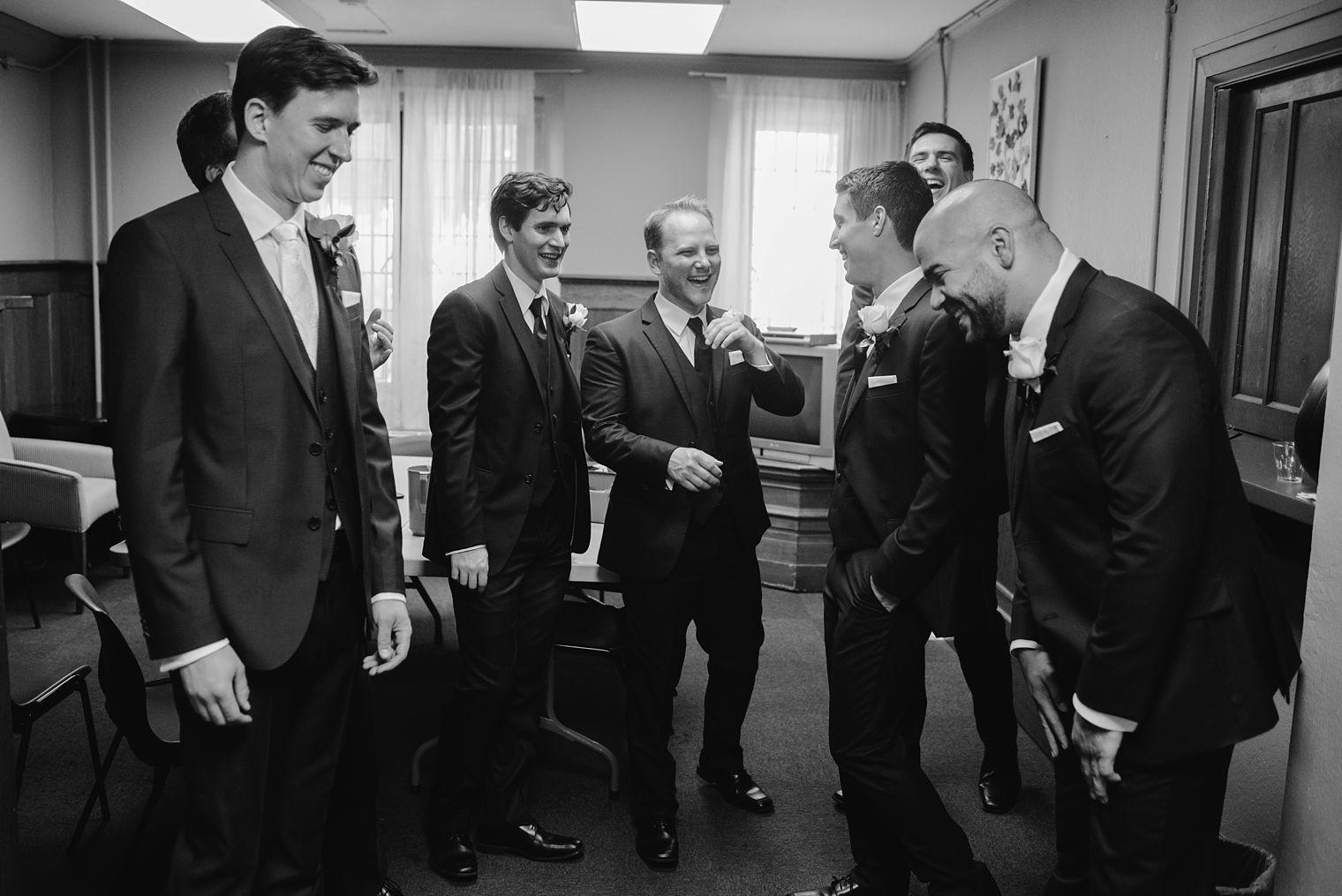 groomsmen laughing at wedding