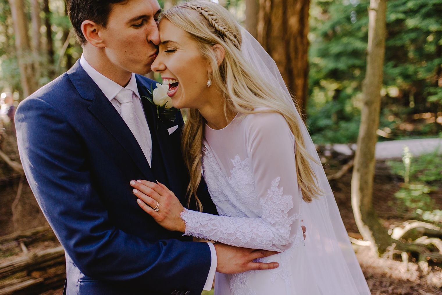wedding couple laughing in forest
